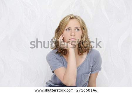 Young woman sitting thoughtful - stock photo