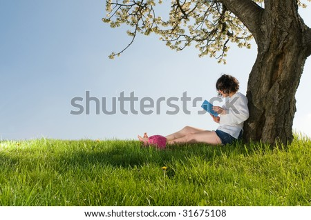 Young woman sitting under a blossom tree reads a book in a beautiful sunny day - stock photo