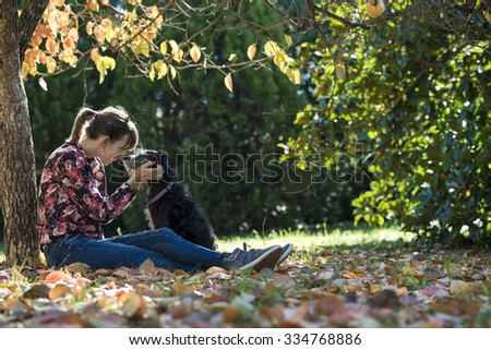 Young woman sitting under a colorful autumn tree lovingly petting her black dog as they join their noses in affection. - stock photo
