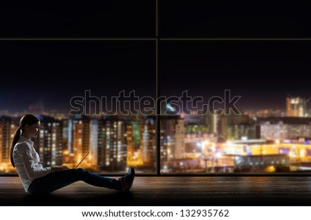 young woman sitting with a laptop by the window with a night city - stock photo