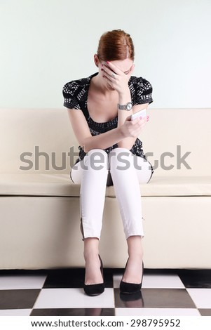 Young woman sitting with hand over her face and holding cell phone with another one - stock photo