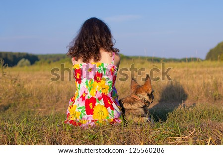 Young woman sitting with her dog  back to camera on the meadow at sunset. - stock photo