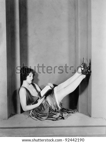Young woman sitting with her legs up and reading - stock photo