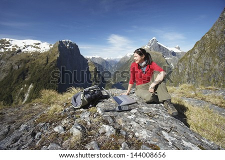 Young woman sitting with laptop on boulder against mountains - stock photo