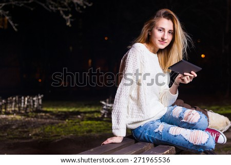Young woman sitting with Tablet and reading from ebook - stock photo