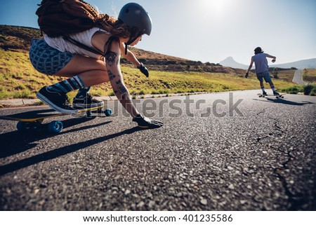 Young woman skating with her friend in background. Young people longboarding on rural road on summer day. - stock photo