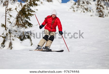 Young woman skiing in mountains - stock photo