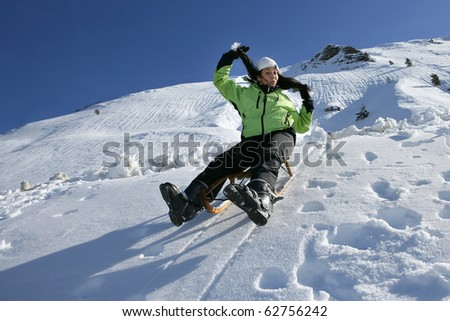 Young woman sledding in snow - stock photo