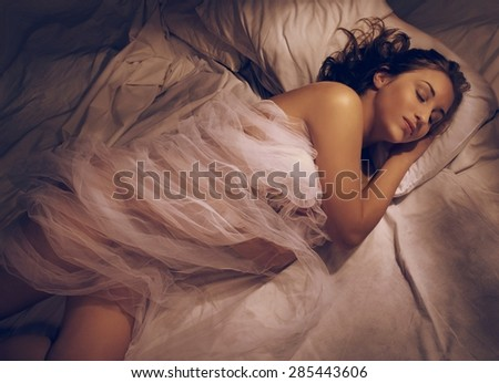 Young woman sleeping at night in bed - stock photo
