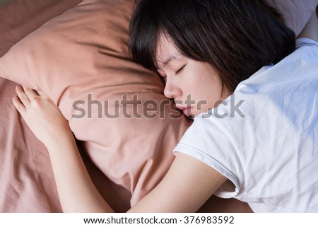 young woman sleeping in bedroom