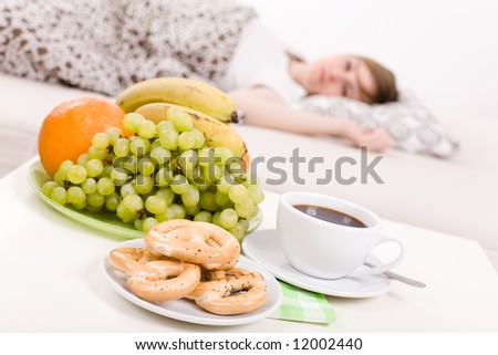 Young woman sleeping in the bed / focus on the fresh breakfast - stock photo