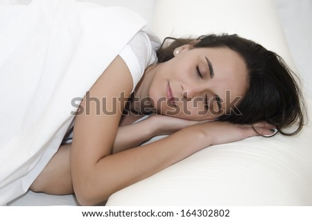 Young woman sleeping in the foreground, with sheets and white background