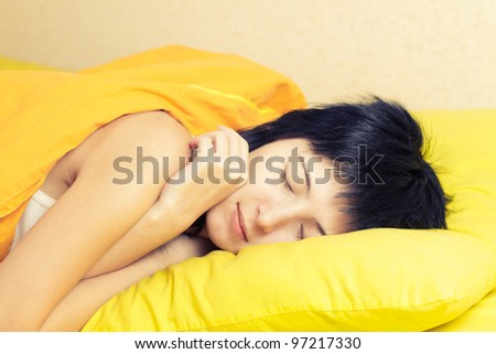 Young woman sleeping in yellow bed