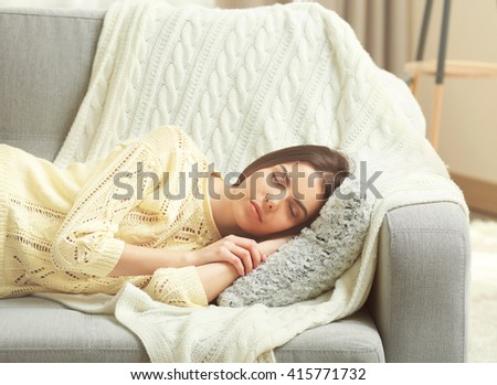 Young woman sleeping on the couch in living room - stock photo