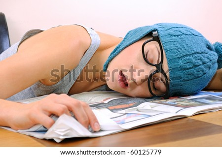 Young woman sleeping on the table - stock photo