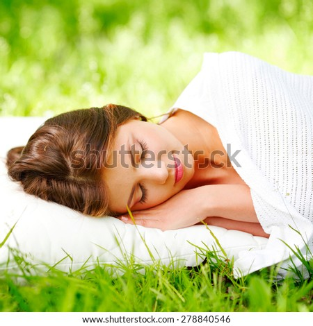 Young woman sleeping on white pillow in fresh spring grass - stock photo