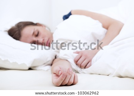 Young woman sleeping soundly in bed, focus on her outstretched hand on the mattress - stock photo