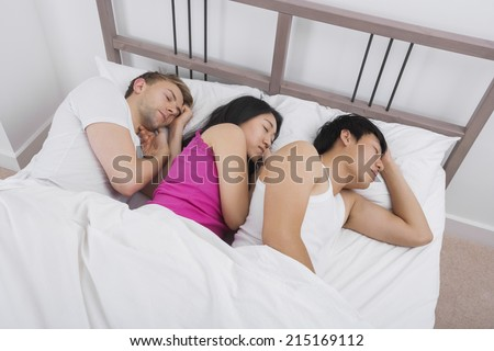 Young woman sleeping with two men in bed - stock photo