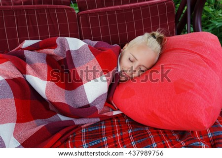 young woman slip on big soft swing in garden on red pillow covered by red checkered blank, horizontal close up - stock photo