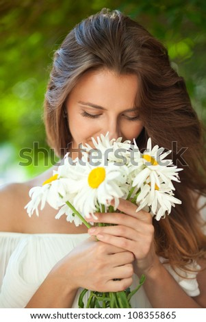 Young woman smelling a bouquet of daisies, which in her hands. Close-up