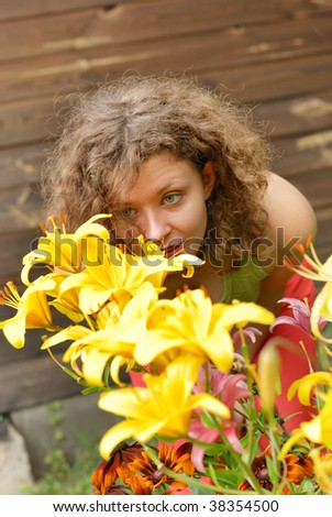 Young woman smelling lilies in garden - stock photo