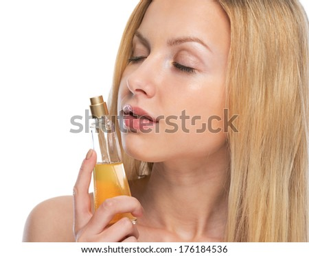 Young woman smelling perfume - stock photo