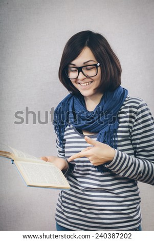 young woman smiles and shows finger in book. - stock photo