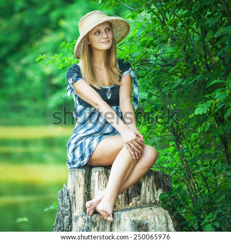 Young woman smiles in straw hat on stub, in summer city park. - stock photo