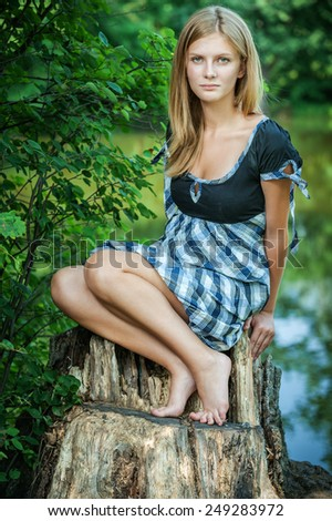 Young woman smiles on stub, in summer city park. - stock photo