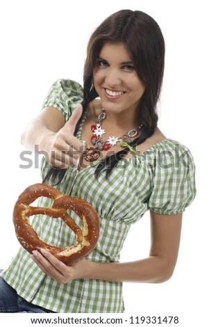 Young woman smiles with a bavarian pretzel and holds her thumb up