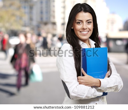 young woman smiling and holding a notebook against a street background - stock photo