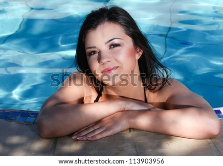 Young woman smiling and standing in the pool and her hands resting on the edge - stock photo
