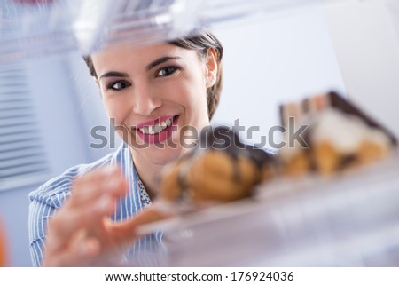 Young woman smiling and taking pastry with chocolate topping from fridge. - stock photo