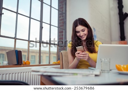 Young woman smiling as she reads an sms on her mobile phone while relaxing at home with her laptop computer