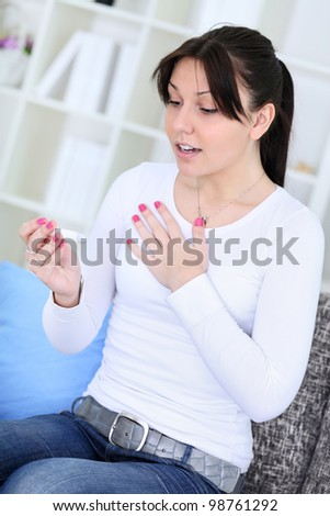 young woman smiling at the results of a pregnancy test - stock photo