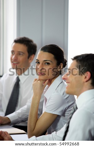 Young woman smiling between businessmen - stock photo
