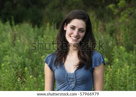 Young woman smiling in a meadow in late afternoon sunlight