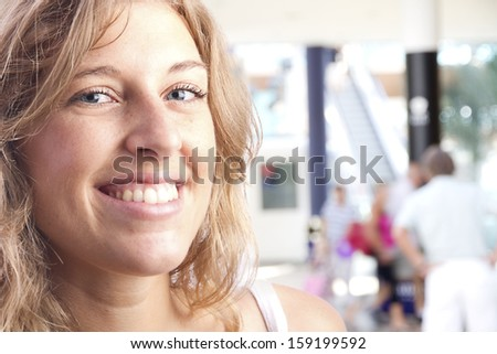 young woman smiling in a shopping center - stock photo