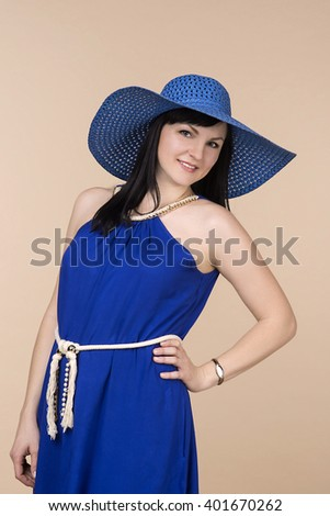 young woman smiling in blue sun hat with fields on beige background. Fashion and beauty. beautiful brunette in blue dress