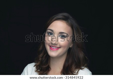 Young woman smiling in front of a black background. - stock photo