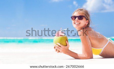 young woman smiling lying in bikini with coconut on beach