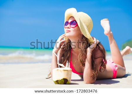 young woman smiling lying in straw hat in sunglasses with coconut on beach - stock photo