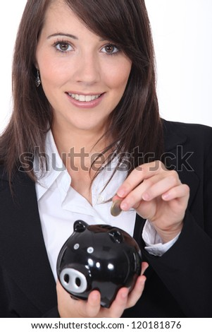 Young woman smiling putting coin in a piggy bank - stock photo