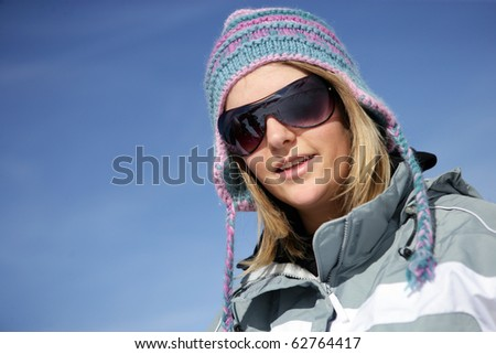 Young woman smiling wearing sunglasses and a wool cap - stock photo