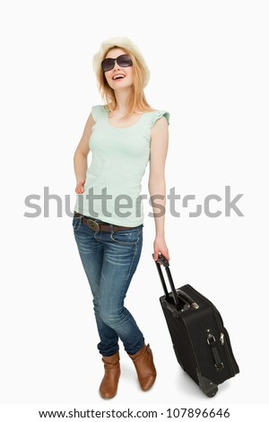 Young woman smiling while holding a suitcase against white background - stock photo