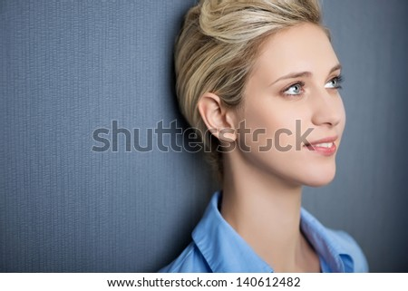 Young woman smiling while looking away against blue wall - stock photo