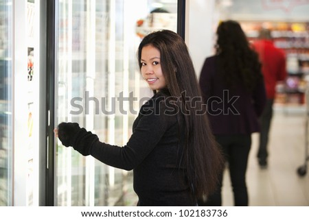 Young woman smiling while opening refrigerator in supermarket with people in the background