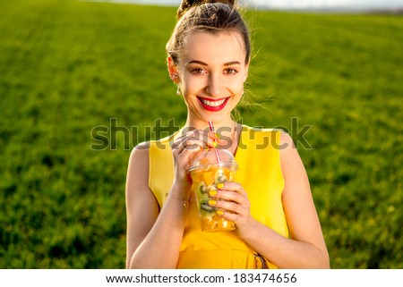 Young woman smiling with fruits in transparent cup on green grass background dressed in yellow wear