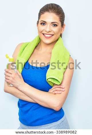 young woman smiling with teeth posing against white wall in sport style with water bottle. isolated portrait. - stock photo