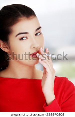 Young woman smoking a cigarette - stock photo